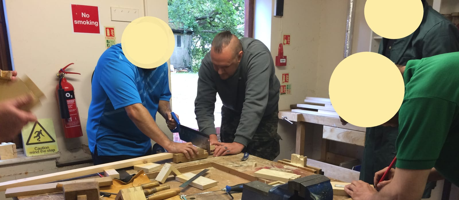 4 people and a tutor doing woodwork in a workshop