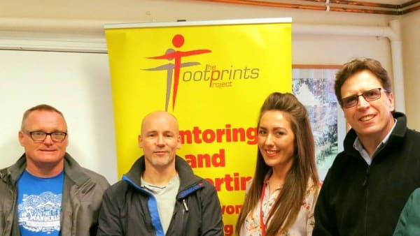 Footprints Staff Team standing against a banner