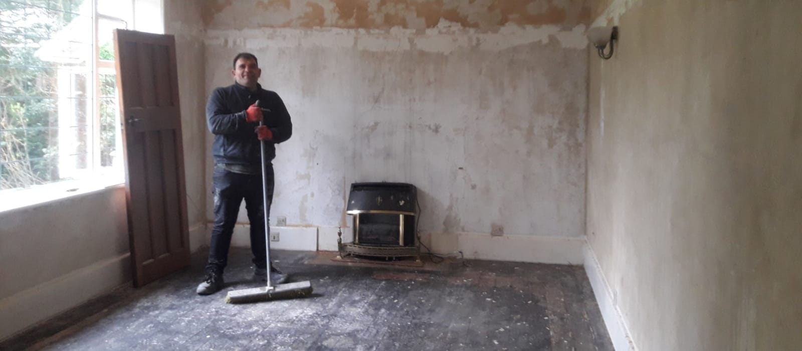 Paul holding a brrom in a large room that has been prepared for decorating